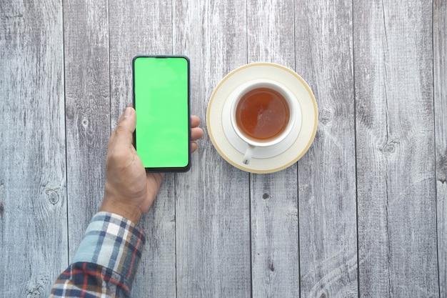 Вид сверху человека, держащего смартфон и пьющего чай