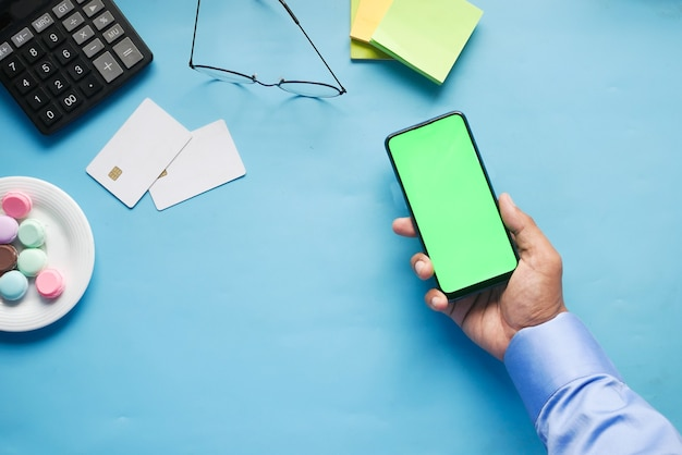 사무실 책상에 빈 화면이 있는 스마트 폰을 들고 있는 남자 손의 상위 뷰