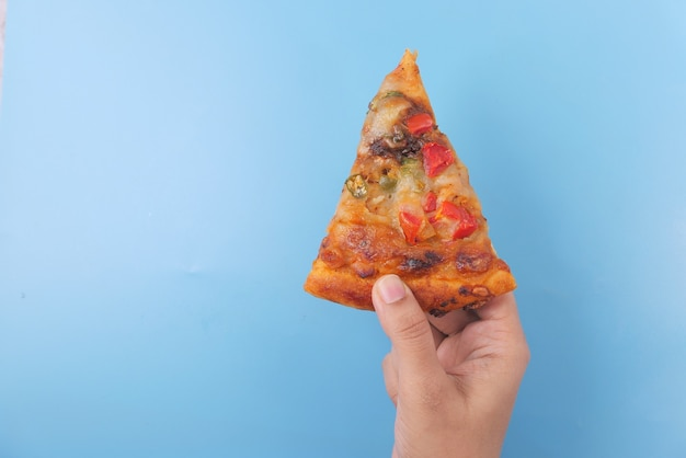 青い背景の上のピザのスライスを手で摘む男の上面図