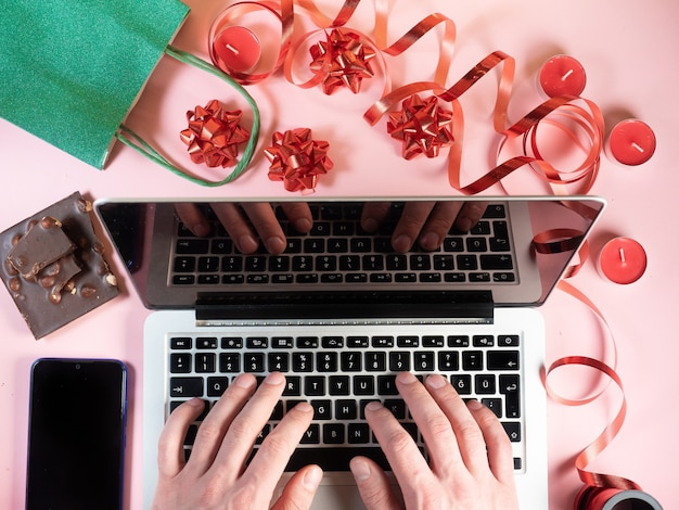 남자의 상위 뷰는 노트북에 손. 크리스마스 장식 배경입니다. 선물, 양초, 초콜릿, 리본 핑크