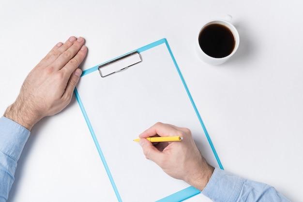 Вид сверху на руки человека, бумаги и чашку кофе