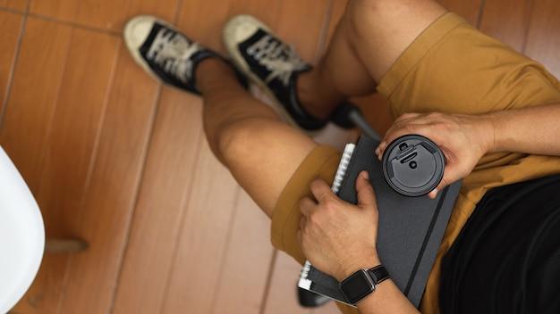 快適な事務室に座っている間コーヒーカップとノートを保持している男のトップビュー
