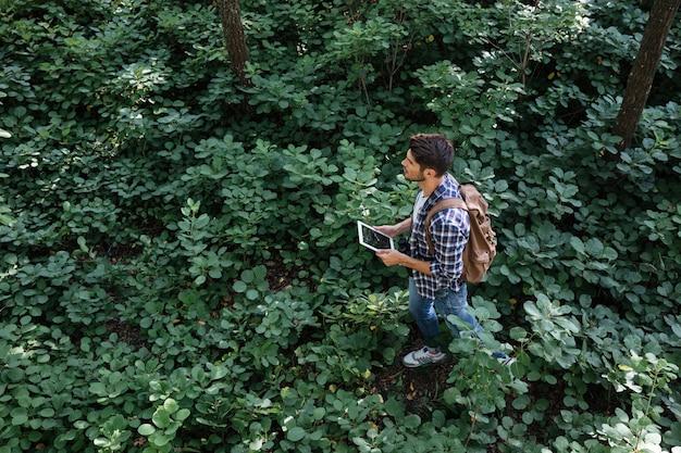 태블릿, 쌍안경, 배낭을 메고 숲을 걷고 있는 셔츠를 입은 남자의 상위 뷰