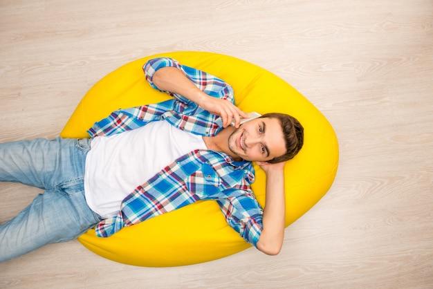 携帯電話で黄色い枕の上に横たわっている男の上面図