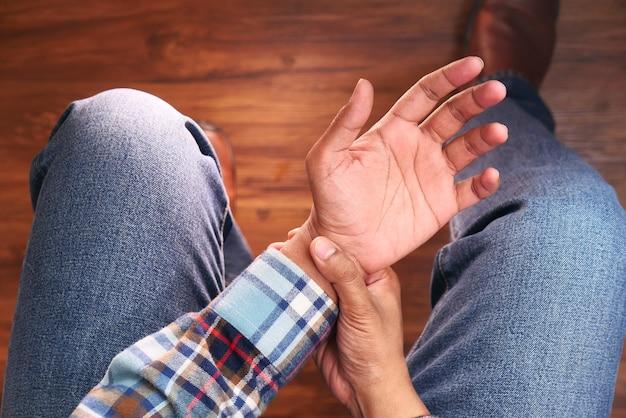 Вид сверху человека, страдающего болью в руке, крупным планом, сидя на стуле