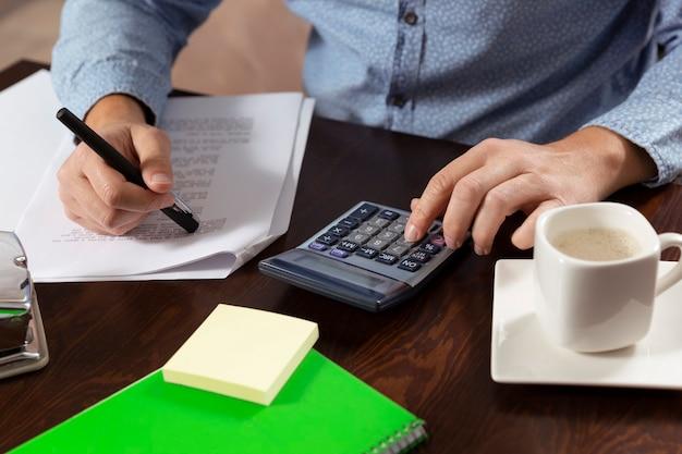 木製の机の上に電卓、ノートブック、コーヒーカップと男の平面図