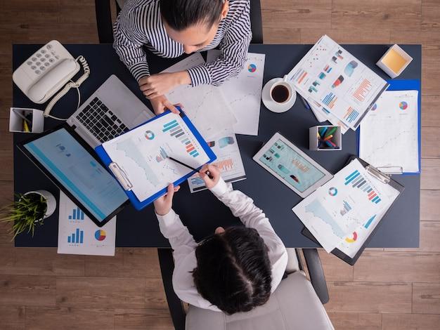 관리자의 상위 뷰는 책상에 앉아 있는 직원에게 재무 전략을 설명합니다.
