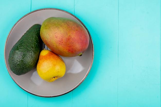 Вид сверху манго с грушей и авокадо на тарелке на синей поверхности