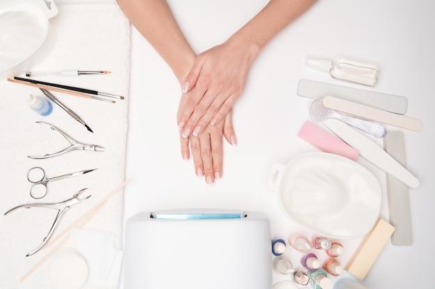 マニキュアツールとマニキュア手順を取得するために彼女の手を準備している女性の上面図