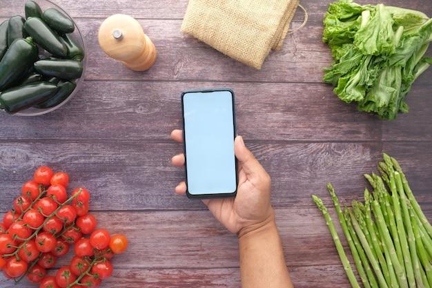 테이블에 신선한 야채와 함께 스마트 폰을 들고 손 망의 상위 뷰