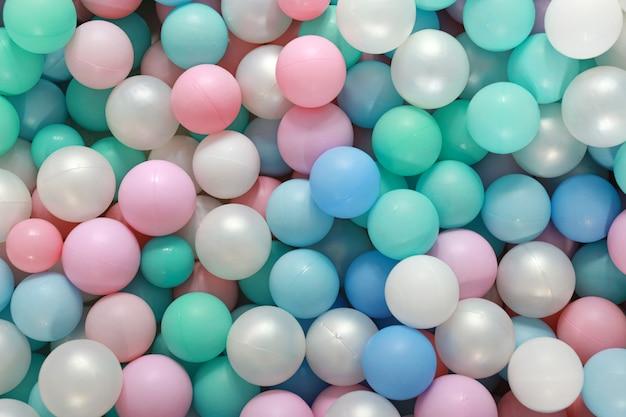 ボールプール内の多くのパステルカラフルなガムボールの平面図。彼らは子供のパーティーのためのプレイルーム屋内遊び場で。背景とテクスチャのコンセプト。