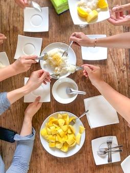多くの人の上面図は、木のテーブルの上でタイの伝統的なデザート「マンゴーともち米」をすくい取ります。