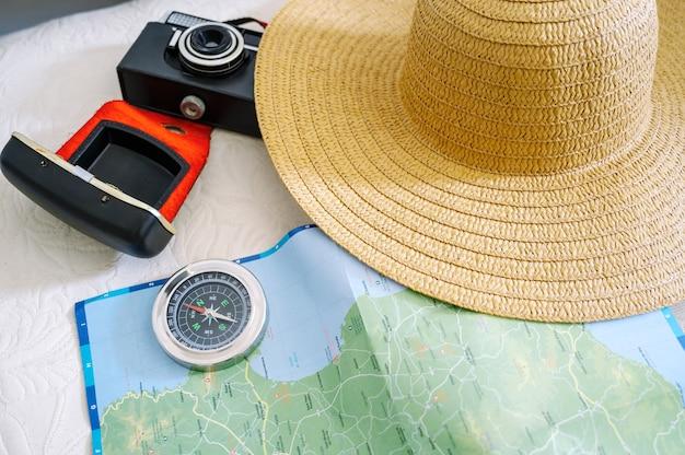 Вид сверху камеры компаса карты и женской шляпы для подготовки поездки