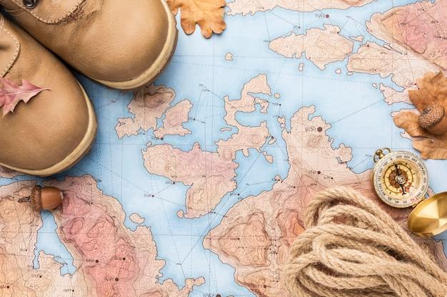 Вид сверху карты с осенними листьями и сапогами