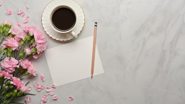 テーブルに飾られた紙、鉛筆、コーヒーカップ、花と大理石の机の上面図