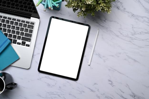 디지털 태블릿, 노트북, 노트북, 식물 및 복사 공간이 있는 대리석 사무실 책상의 최고 전망.