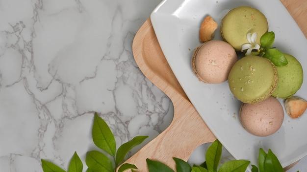 コピースペースと葉で飾られたフランスのカラフルなマカロンのプレートと大理石のテーブルの上面図