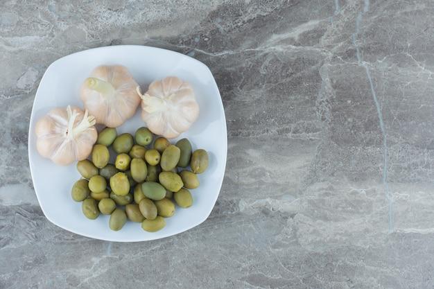 Вид сверху маринованных зеленых оливок и чеснока на белой тарелке.