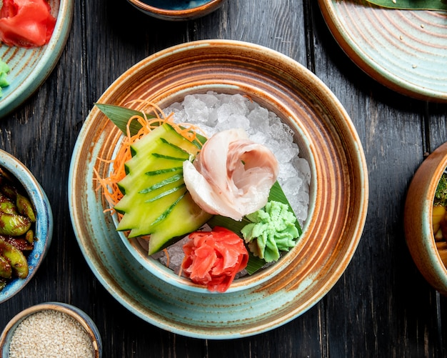 Вид сверху филе маринованной сельди с нарезанными огурцами имбирем и соусом васаби на кубиках льда в тарелке на деревянном столе