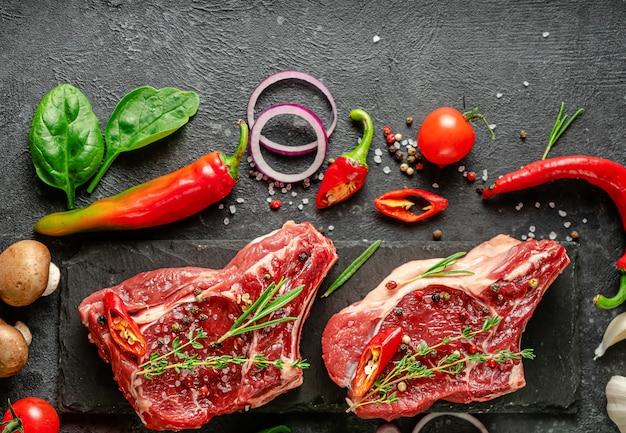 Вид сверху маринованных сырых стейков из телятины с кулинарными ингредиентами