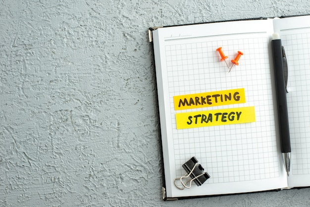 Вид сверху ручки сочинений маркетинговой стратегии и открытой спиральной записной книжки на сером фоне песка
