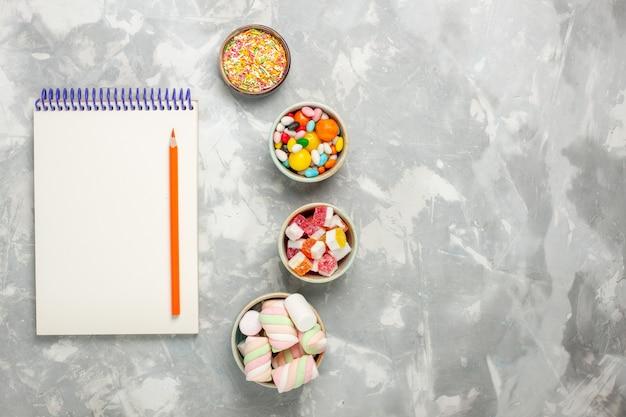 흰색 표면에 메모장으로 마시맬로와 사탕의 상위 뷰