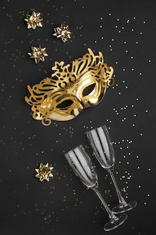Вид сверху маски для карнавала с блеском и бокалами шампанского