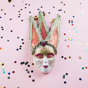 Top view of masquerade carnival mask with glossy decoration material over pink background