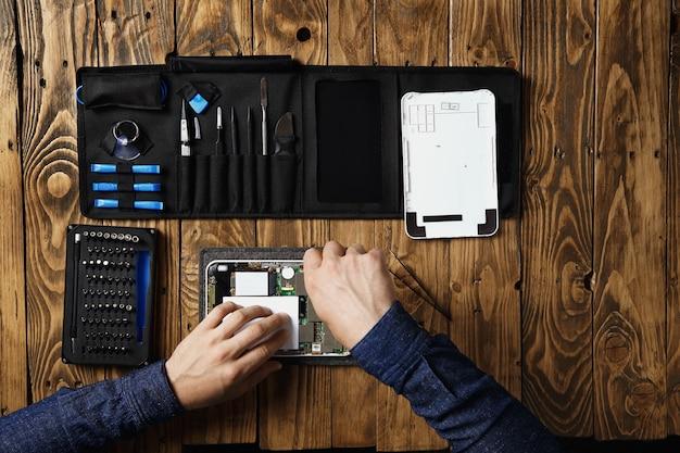 마스터의 상위 뷰는 깨진 태블릿에서 작동하여 도구 가방 근처와 서비스 실험실의 나무 테이블에서 수리합니다.