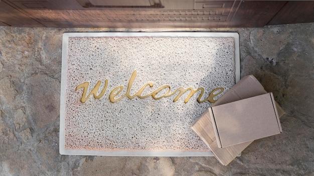 Вид сверху коврика с приветственным сообщением и пакетами
