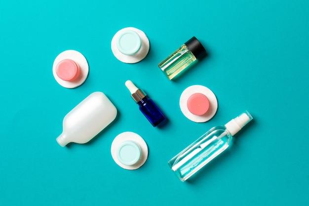 フェイスケアの手段の上面図:トニックのボトルとジャー、ミセル洗浄水、クリーム、色付きの背景のコットンパッド。あなたのアイデアのための空のcpaceとボディケアの概念。