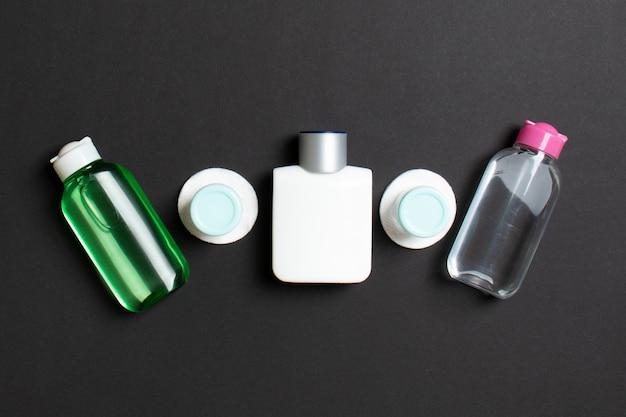 フェイスケアの手段の上面図:トニックのボトルとジャー、ミセルクレンジングウォーター、クリーム、色付きの表面のコットンパッド