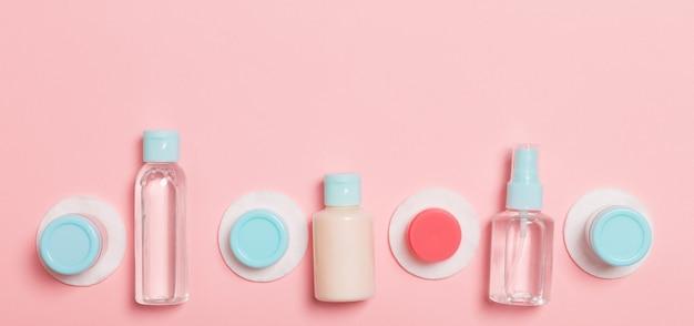 フェイスケアの手段の上面図:トニックのボトルとジャー、ミセルクレンジングウォーター、クリーム、ピンクの背景のコットンパッド。あなたのアイデアのための空のcpaceとボディケアの概念