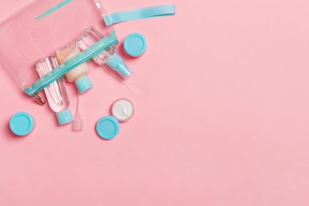フェイスケアの手段の上面図:トニックのボトルとジャー、ミセルクレンジングウォーター、クリーム、ピンクの表面のコットンパッド。