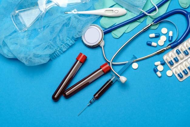 Вид сверху медицинского оборудования и инструментов на синем фоне - стетоскоп, хирургическая маска, медицинские перчатки, шприц и пробирка для анализа крови - концепция здравоохранения и медицины.