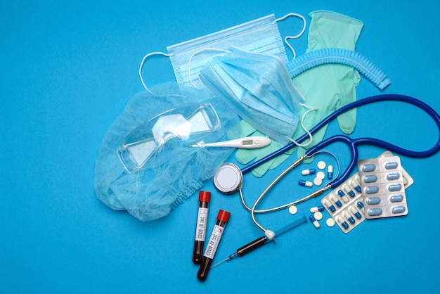 Вид сверху медицинского оборудования и инструментов на синем фоне - стетоскоп, хирургическая маска, медицинские
