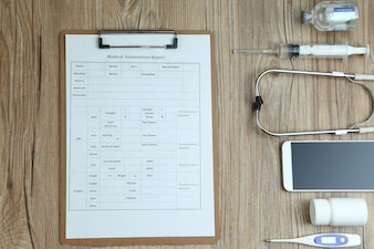 Top view of medical examination report,cellphone,and medical equipments on wooden desk
