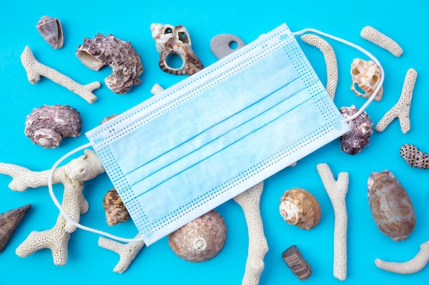 Вид сверху медицинской маски для лица и ракушек на синем. плоская планировка