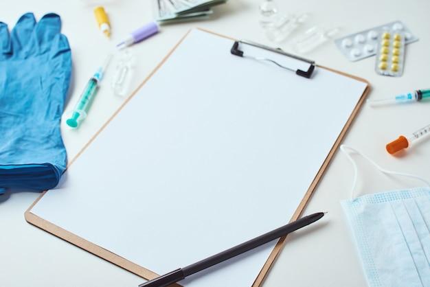 Взгляд сверху медицинских деталей и пустого бумажного чистого листа на белой предпосылке. концепция здравоохранения и медицины