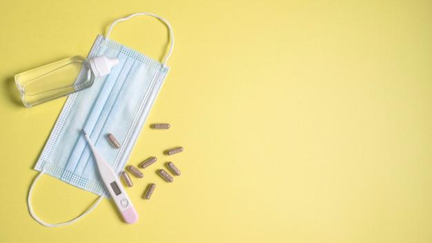 Вид сверху медицинской маски с термометром и таблетками