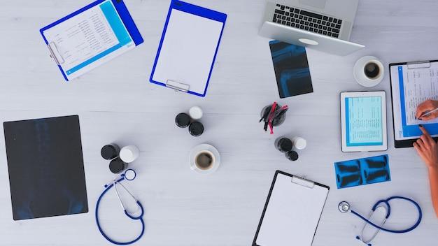 태블릿을 사용하여 약속을 확인하는 의사의 상위 뷰, x- 레이 및 의료 장비가있는 클리닉 책상에 앉아 클립 보드에 메모를 시침