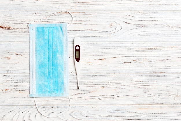 白い木製の医療用防護マスクとデジタル温度計の平面図です。