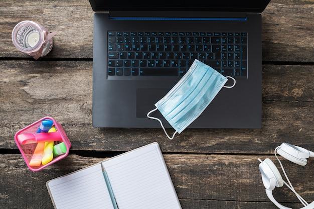 机の上にメモ帳、カラフルなマーカー、ヘッドフォンを備えたラップトップコンピューターの医療用保護マスクの上面図