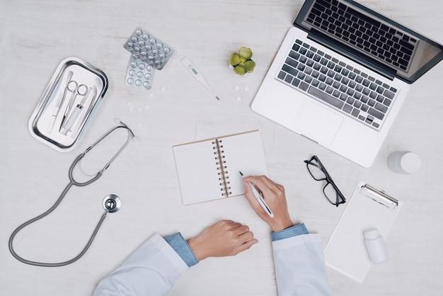 Вид сверху руки врача медицины, работающей на столе.