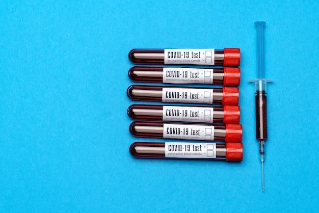 Взгляд сверху пробирок медицины с образцами крови и шприцем над голубой предпосылкой.