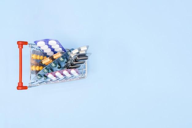 Вид сверху лекарств в магазинной тележке на синем фоне с копией пространства.