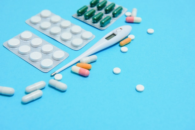 医薬品、作業工具、付属品の医師、看護師の上面図。医療セット-青色の背景に錠剤、温度計、注射器、アンプル、絆創膏、スタトスコープ。フラットレイ