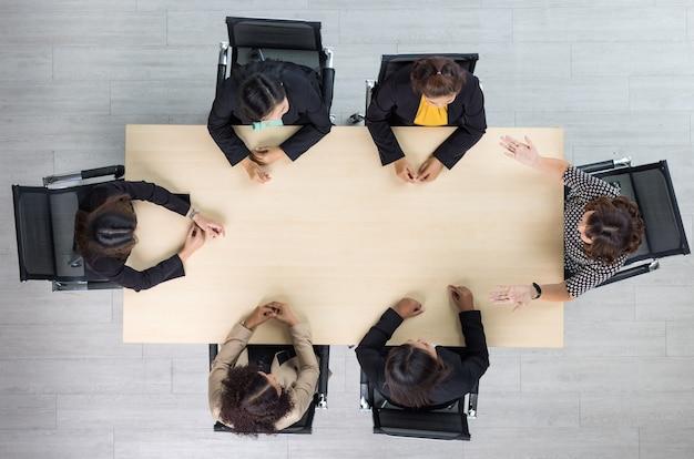 会議室でのチームワークでビジネスについて話し合ったり話したりする6人のエグゼクティブビジネスウーマンが各椅子に座っている会議会議用木製テーブルの上面図。