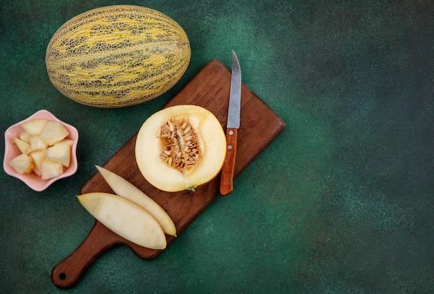Вид сверху дыни на деревянной кухонной доске с ножом с кожурой на зеленой поверхности