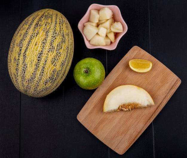 Вид сверху ломтика дыни на деревянной кухонной доске с зеленым яблоком с ломтиками на розовой миске на черной поверхности